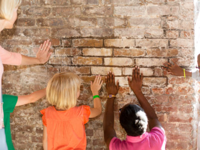 Children curiously touching the bricks of the Charterhouse