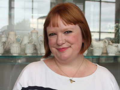 Jenny Wedgbury smiling in front of a display case of white crockery.