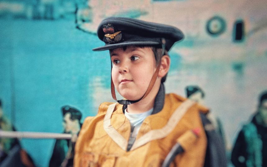 A young boy wearing an RAF uniform worn by aircrew in the 1940s.