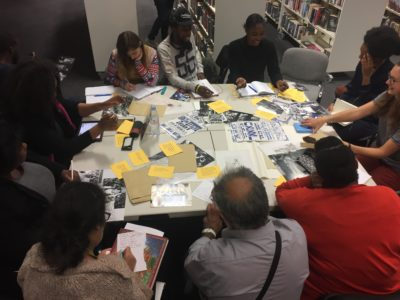A diverse poetry group of men and women exploring archival images from UCL Special Collections in Stratford Library.
