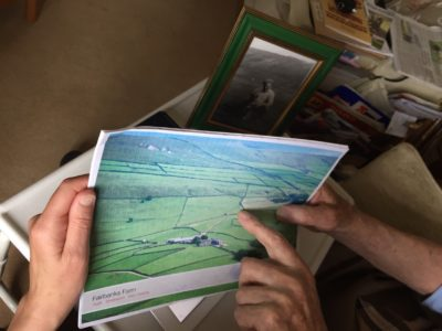 Someone showing and pointing at a photo of Fairbanks farm
